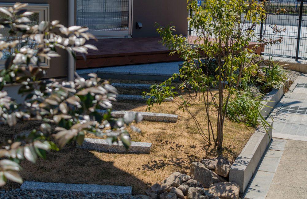 ガレージ後ろのウッドデッキのある庭